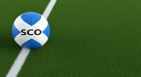 Bola de futebol em cores nacionais de Scotlands em um campo de futebol Copie o espaço no lado direito Foto de Stock Royalty Free