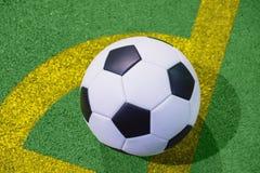 Bola de futebol em uma linha do pontapé de canto em uma opinião superior artificial de grama verde Fotografia de Stock Royalty Free
