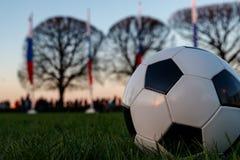 A bola de futebol encontra-se na grama No fundo você pode ver muitas bandeiras do russo imagem de stock royalty free