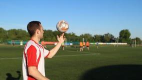 Bola de futebol de equilíbrio do jogador em seu dedo vídeos de arquivo