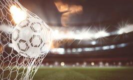 A bola de futebol marca um objetivo na rede rendição 3d Fotos de Stock