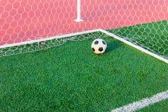 Bola de futebol na grama verde na rede do objetivo Imagens de Stock Royalty Free