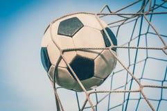 Bola de futebol na rede do objetivo com fundo do céu azul Imagens de Stock