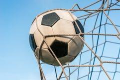 Bola de futebol na rede do objetivo com fundo do céu azul Foto de Stock