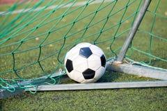Bola de futebol na rede do objetivo no campo de futebol Fotografia de Stock