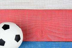 Bola de futebol na tabela vermelha, branca e azul Foto de Stock