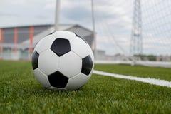 Bola de futebol no gramado verde perto da porta da porta imagens de stock