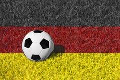 Bola de futebol ou bola do futebol no campo preto vermelho/amarelo, bandeira de Alemanha Imagens de Stock Royalty Free