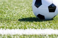 Bola de futebol que senta-se na grama perto da linha Fotografia de Stock