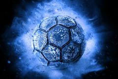 Bola de futebol velha dentro no fundo azul fotografia de stock