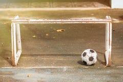 Bola de futebol velha no assoalho do cimento imagens de stock royalty free
