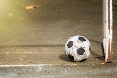 Bola de futebol velha no assoalho do cimento foto de stock royalty free