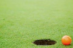 Bola de golfe alaranjada no verde de colocação Imagens de Stock Royalty Free