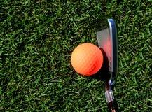 Bola de golfe alaranjada pronta para ser batido por um clube de golfe fotografia de stock royalty free