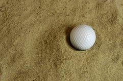 Bola de golfe cercada pela areia Fotografia de Stock Royalty Free