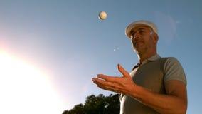 Bola de golfe de jogo e de travamento do jogador de golfe no curso video estoque