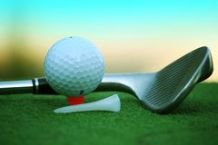 Bola de golfe e clube de golfe no campo de golfe da noite com luz do sol Imagens de Stock