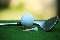 Bola de golfe e clube de golfe no campo de golfe da noite com luz do sol Foto de Stock Royalty Free