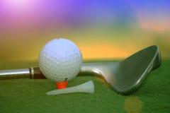 Bola de golfe e clube de golfe no campo de golfe da noite com luz do sol Imagem de Stock