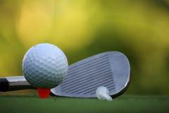 Bola de golfe e clube de golfe no campo de golfe da noite com luz do sol Fotografia de Stock