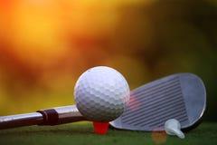 Bola de golfe e clube de golfe no campo de golfe da noite com luz do sol Fotos de Stock