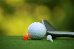 Bola de golfe e clube de golfe no campo de golfe da noite com luz do sol Fotos de Stock Royalty Free