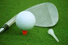 Bola de golfe e clube de golfe no campo de golfe da noite com luz do sol Fotografia de Stock Royalty Free