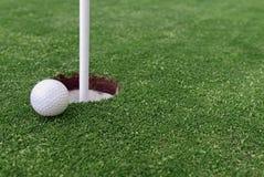 Bola de golfe e Flagstick da grama Manicured do verde de colocação Imagem de Stock