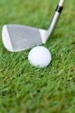 A bola de golfe e o ferro na grama verde detalham o macro Fotografia de Stock