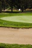 Bola de golfe em um perigo da armadilha de areia do depósito greenside em cours de um golfe Imagem de Stock Royalty Free
