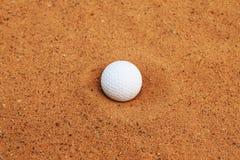 Bola de golfe na areia vermelha imagens de stock royalty free