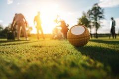 Bola de golfe na grama e nas silhuetas dos jogadores de golfe que jogam atrás Imagens de Stock Royalty Free