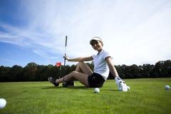 Bola de golfe na grama verde sobre um fundo azul Imagens de Stock