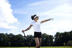 Bola de golfe na grama verde sobre um fundo azul Fotos de Stock