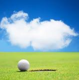 Bola de golfe no furo com céu bonito Fotografia de Stock Royalty Free