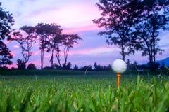 Bola de golfe no T no T fora com primeiro plano da grama verde do borr?o e para borrar o c?u colorido com fundo das ?rvores da si foto de stock royalty free