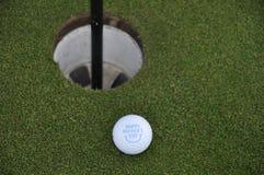 Bola de golfe no verde do golfe Imagem de Stock