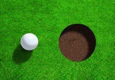 Bola de golfe perto do furo com espaço da cópia Fotografia de Stock Royalty Free
