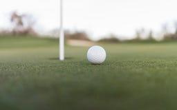 Bola de golfe perto do furo do copo no verde de colocação Fotografia de Stock