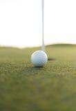 Bola de golfe perto do furo do copo no verde de colocação Imagens de Stock Royalty Free