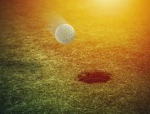 Bola de golfe perto do furo em um campo de grama imagem de stock