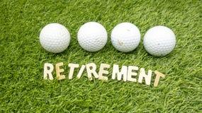 A bola de golfe quatro está na grama verde com palavra da aposentadoria imagem de stock royalty free