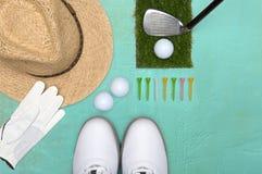 Bola de golfe, sapatas do golfe, T e chapéu de palha em uma base na luz - verde de cima de imagens de stock
