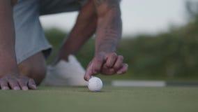 Bola de golfe de sopro do homem oriental considerável do homem no furo e nos polegares das mostras acima Lazer do ver?o video estoque