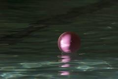 Bola de goma rosada que flota en agua con puntos culminantes verdes Imagenes de archivo