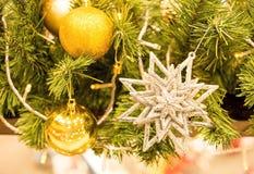 Bola de la estrella del oro y del oro adornada en el árbol de Chirstmas imagenes de archivo