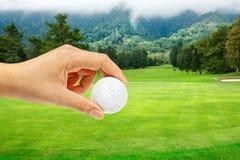 Bola de la explotación agrícola de la mano en campo de golf Fotos de archivo libres de regalías