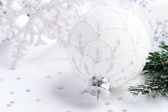 Bola de la Navidad blanca, rama del abeto y copo de nieve en el bacground blanco Imagen de archivo libre de regalías