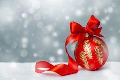 Bola de la Navidad con el arqueamiento y la cinta rojos Imágenes de archivo libres de regalías