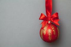 Bola de la Navidad con el arqueamiento y la cinta rojos Imagenes de archivo